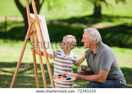 Grandfather and his grandson painting in the garden - stock photo