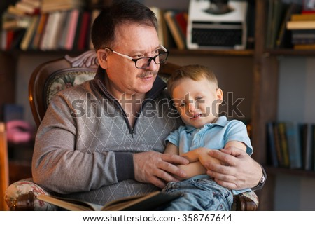 grandfather and his grandson sitting in armchair with book - stock photo
