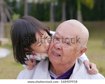 grandfather and his little granddaughter together in garden - stock photo