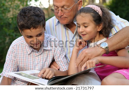 Grandfather and kids reading book outdoors