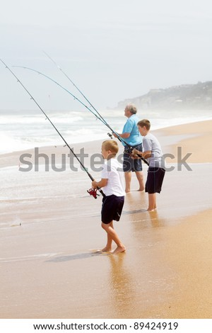 grandfather and two grandsons fishing on beach - stock photo