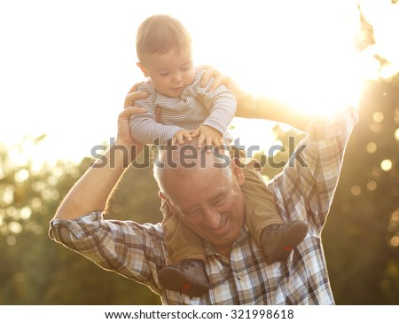 Grandfather carrying grandson on shoulders in park on sunny autumn day  - stock photo