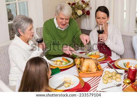 Grandfather carving chicken while women drinking red wine at home in the living room - stock photo