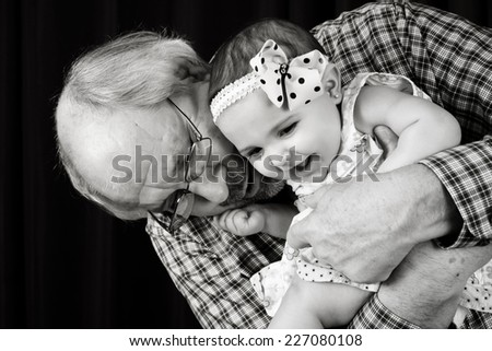 Grandfather cuddling his laughing baby granddaughter wearing headband - stock photo