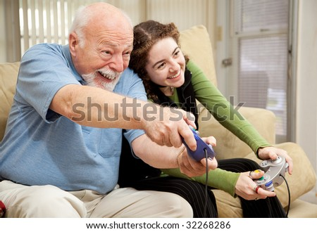 Grandfather enjoys playing video games with his teenage granddaughter.