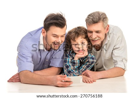 Grandfather, father and son lying and using a phone, isolated a white background. - stock photo