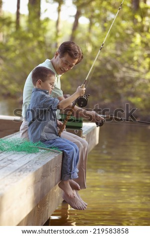 Grandfather fishing with grandson - stock photo