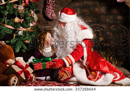 Grandfather Frost gives a gift a little girl sitting in a chair. Fireplace and Christmas tree in the background