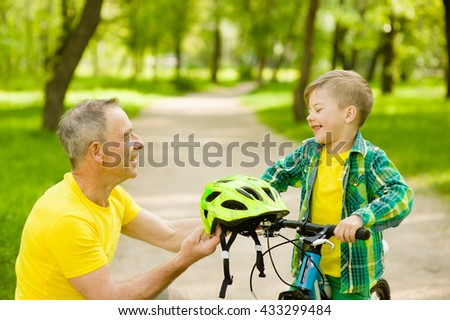 Grandfather gives his grandson a bicycle helmet.