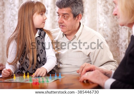 grandfather, grandmother with her granddaughter in the house playing board games (Man do not be angry) - stock photo