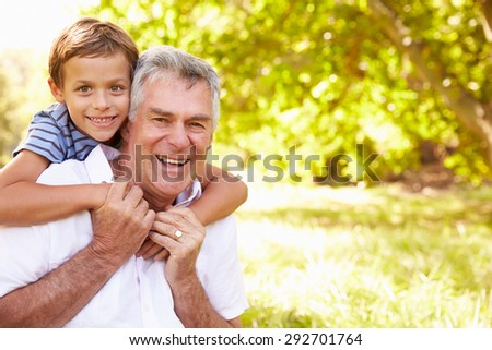 Grandfather having fun outdoors with his grandson, portrait - stock photo