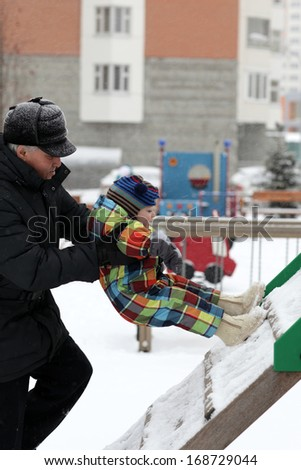 Grandfather helping his grandson to climb the slide in winter - stock photo