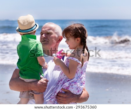 grandfather holding his grandkids on a beach vacation