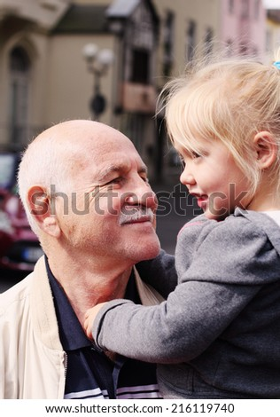 grandfather holding his 3 year old granddaughter - stock photo