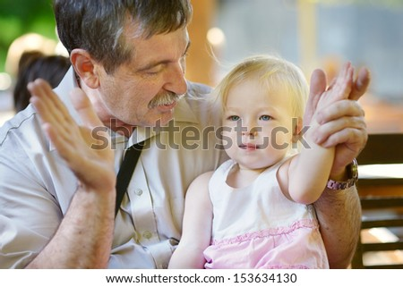 Grandfather hugging his toddler granddaughter - stock photo