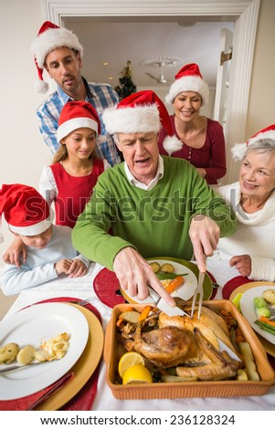 Grandfather in santa hat carving chicken during dinner at home in the living room - stock photo