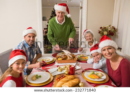 Grandfather in santa hat carving roast turkey at christmas dinner at home in the living room - stock photo