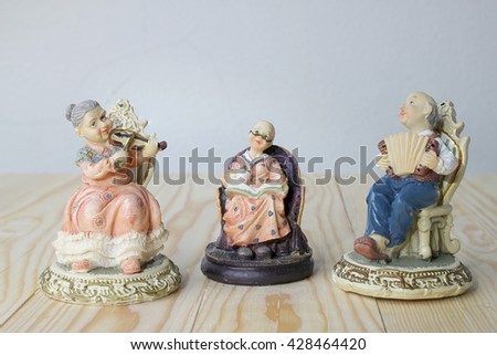 grandfather is playing Accordion with grandmother is playing violin and reading a book dolls on pine wood background. -ceramic doll
