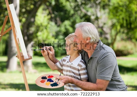 Grandfather painting with his grandson - stock photo