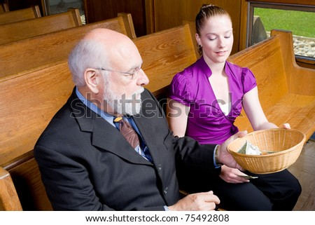 Grandfather passing offering basket to granddaughter in church pew. - stock photo