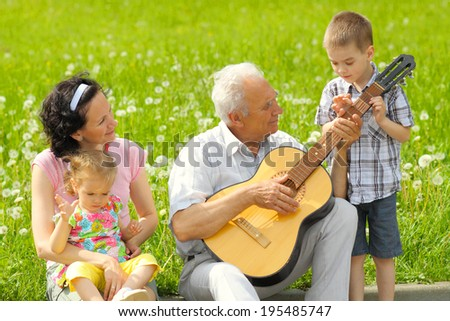 Grandfather playing guitar to his daughter and grandchildren outdoors. romantic portrait of three generations with the guitar.
