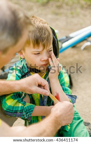 Grandfather putting band-aid on young boy's injury who fell off his bicycle - stock photo