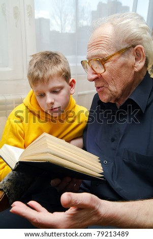 grandfather reading book aloud to his grandson, who is listening to him with attention - stock photo