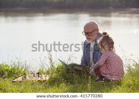 Grandfather reading fairy tale to granddaughter outdoors - stock photo