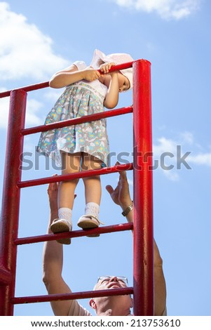 Grandfather supporting a little girl climbing a stairs - stock photo
