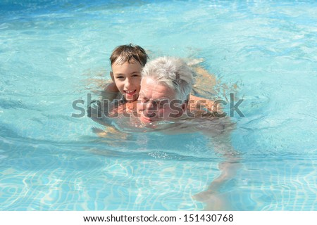 Grandfather swimming with grandson in a blue pool - stock photo