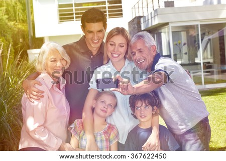 Grandfather taking selfie of a family with smartphone in a garden in summer - stock photo