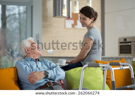 Grandfather talking with loved granddaughter in his home - stock photo