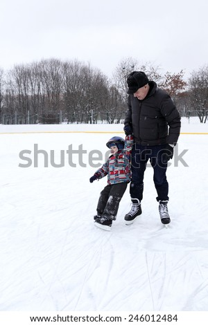 Grandfather teaches his grandson to skate at the outdoor skating rink - stock photo