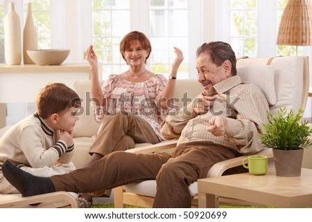 Grandfather telling tales to his grandson, happy grandmother watching in background. - stock photo
