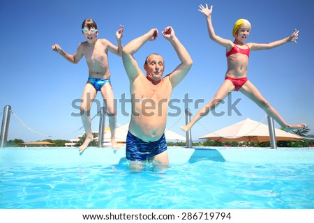 Grandfather with boy and girl jumping into a pool of water - stock photo