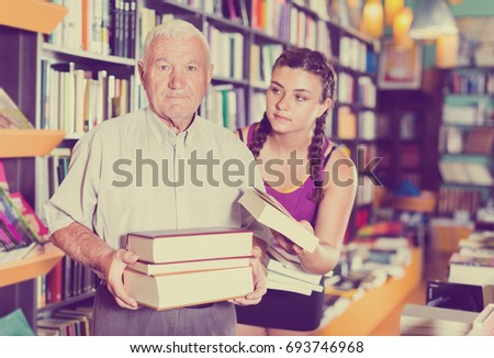 Grandfather with granddaughter are choosing books in bookstore.