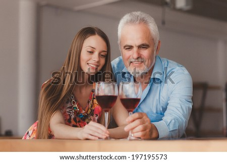 grandfather with his granddaughter drinking wine  in the kitchen