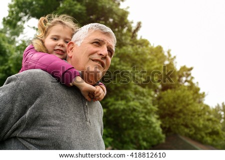 Grandfather with his granddaughter in the park.  Little girl looking at camera. Focus on grandpa.  - stock photo