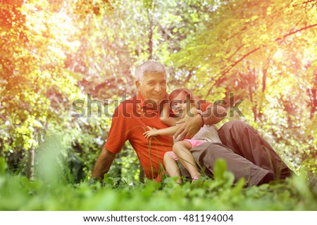 Grandfather with his granddaughter in the park sitting on grass and looking at camera.