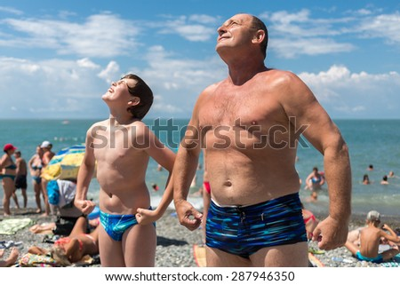 Grandfather with his grandson bask in the sun on the beach - stock photo