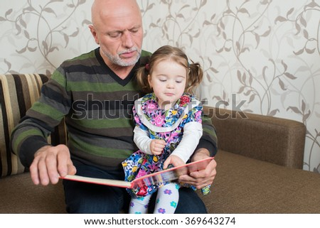Grandfather with his little granddaughter reading a book - stock photo