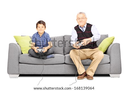 Grandfather with his nephew seated on a sofa playing video games isolated on white background - stock photo