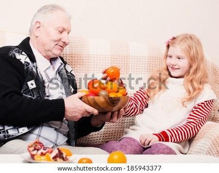 Grandfather with smile girl eating fruits at home