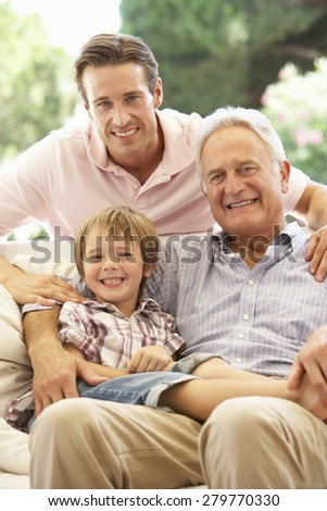Grandfather With Son And Grandson Laughing Together On Sofa - stock photo