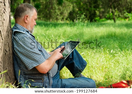 grandfather with the tablet sitting on the grass - stock photo
