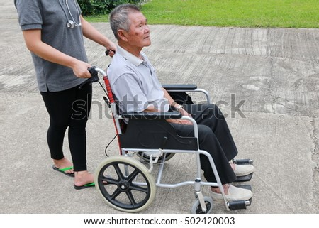 grandfather with wheelchair assisted by nurse outdoor.  a happy senior man on a wheelchair and young caregiver in the park