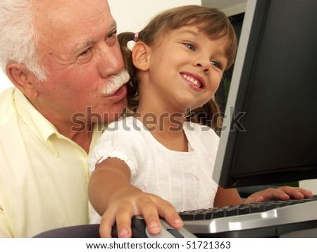grandfathers and granddaughter in a computer. - stock photo