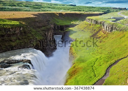 Grandiose Gullfoss in Iceland. In July raging water is shined with the bright morning sun. River banks grew with a green northern moss