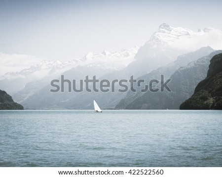 Grandiose mountain landscape. Mountain tops in the snow. White sail on a romantic lake. Bleach Bypass effect.