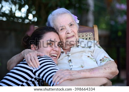 grandma and grandaughter smiling and hugging  - stock photo